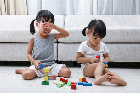 дети: Азиатские китайские маленькие сестры борются за блоки на полу в гостиной дома. Фото со стока