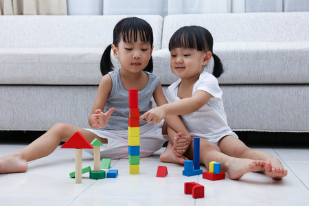 Asian Chinese little sisters playing blocks on the floor in the living room at home. Imagens