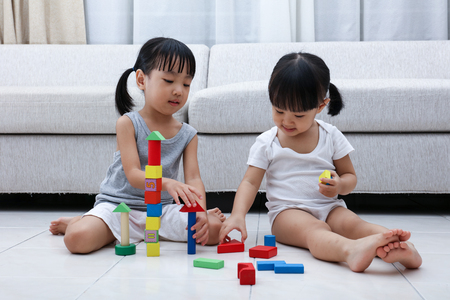 Asian Chinese little sisters playing blocks on the floor in the living room at home. Stock Photo