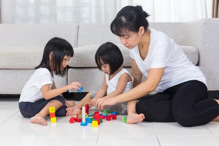 Madre e figlia asiatici cinesi giocano blocchi sul pavimento nel salotto a casa. Archivio Fotografico - 66527164