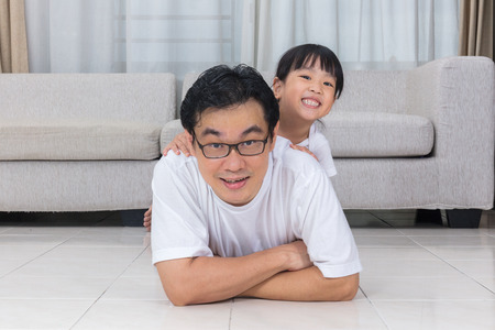 Happy Asian Chinese father and daughters lying on the floor in the living room at home.