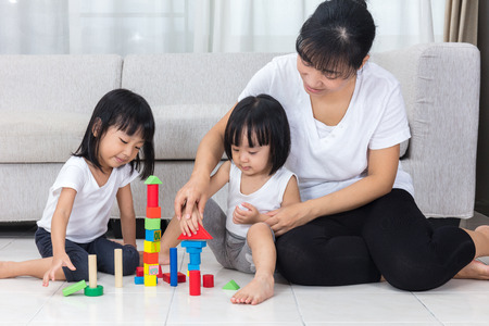 Asian Chinese mother and daughter playing blocks on the floor in the living room at home.
