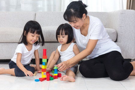 family together: Asian Chinese mother and daughter playing blocks on the floor in the living room at home.