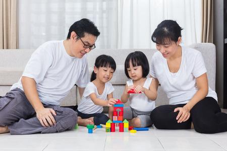 アジア中国の親と娘の自宅のリビング ルームの床にブロックを再生します。