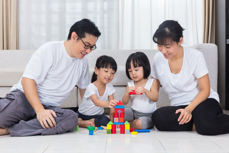 Asian Chinese parents and daughters playing blocks on the floor in the living room at home.