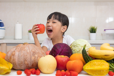 eating food: Asian Chinese little girl eating apple infront fruit and vegetable in the kitchen at home.