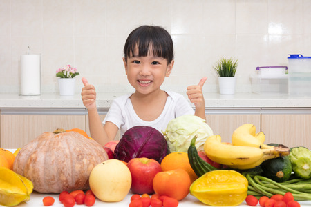 child smile: Asian Chinese little girl thumbs up with fruit and vegetable in the kitchen at home. Stock Photo