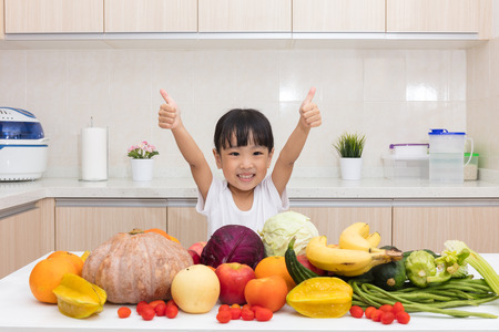 asia children: Asian Chinese little girl thumbs up with fruit and vegetable in the kitchen at home. Stock Photo