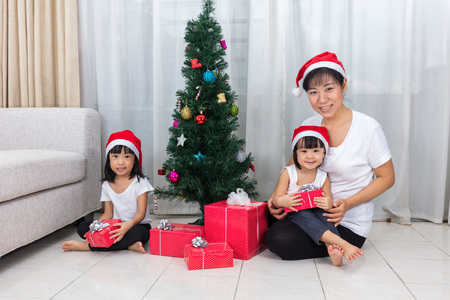 celebrate year: Asian Chinese mother and daughters sitting next to Christmas tree to celebrate Christmas and New Year.