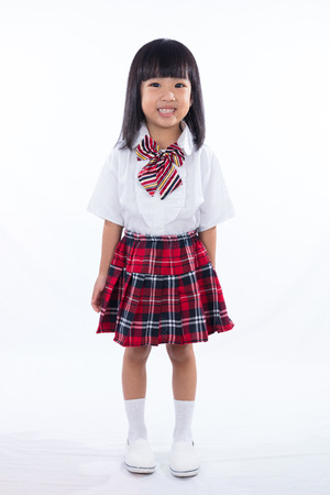 Happy Asian Chinese little girl wearing student uniform in isolated white background Stock Photo