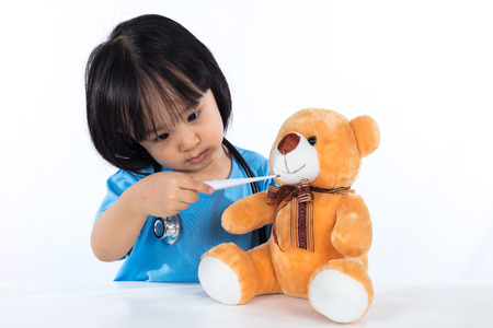 Asian Chinese little girl examine teddy bear with thermometer in isolated white background. Stock Photo