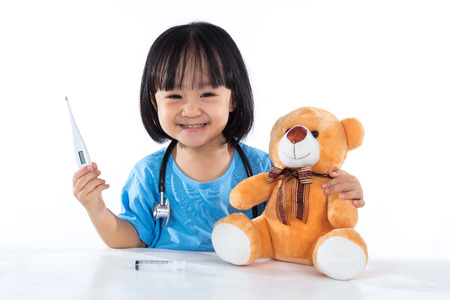 Happy Asian Chinese little girl examine teddy bear with thermometer in isolated white background. Stock Photo