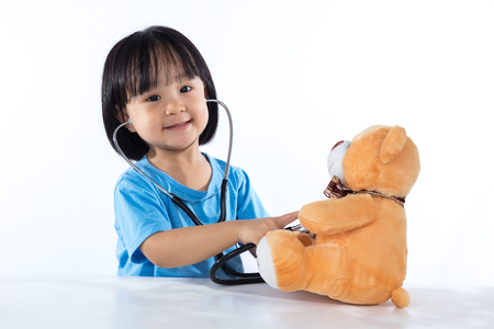 Happy Asian Chinese little doctor girl examine teddy bear in isolated white background.
