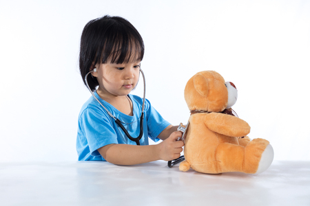 examine: Asian Chinese little doctor girl examine teddy bear in isolated white background.
