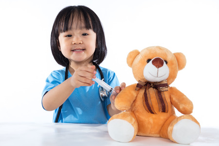 Asian Chinese little doctor girl giving injection to teddy bear in isolated white background.