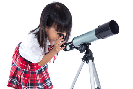 Asian Chinese little girl looking through telescope in isolated white background. Stock Photo