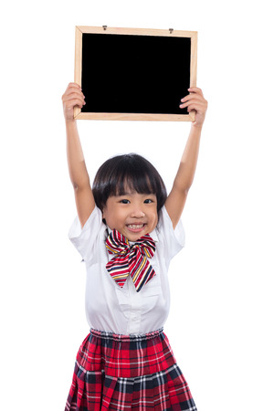 Happy Asian Chinese little girl holding blackboard in isolated white background.