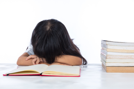 Tired Asian Chinese little girl lying on desk with books in isolated white background.