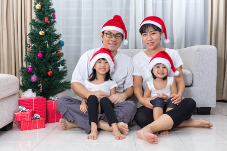 Happy Asian Chinese family sitting on the floor celebrating Christmas in the living room at home with Santa Claus Hat. Stock Photo