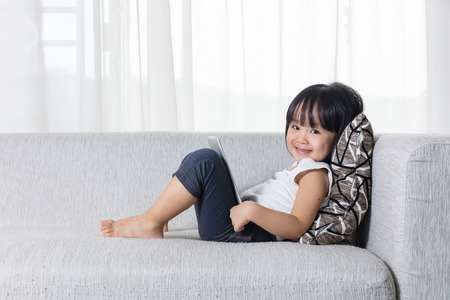 Happy Asian Chinese little girl lying on the sofa with tablet in the living room at home