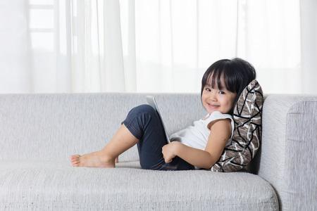 Gelukkig Aziatisch Chinees meisje die op de bank met tablet in de woonkamer thuis liggen