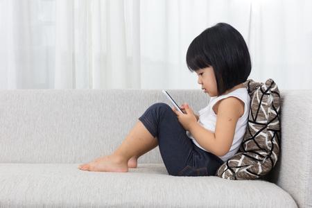Chiński azjatyckich dziewczynka leżącego na kanapie z telefonu komórkowego w salonie w domu.