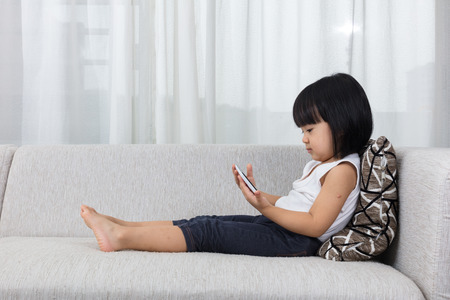 Asian Chinese little girl lying on the sofa with mobile phone in the living room at home.