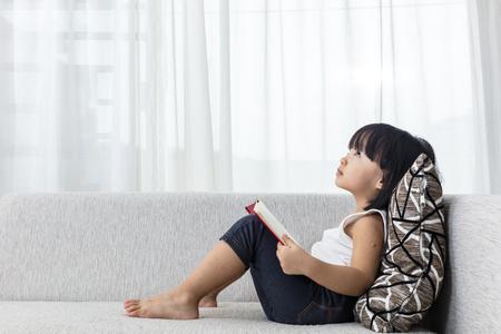 自宅のリビング ルームのソファの上を読みながら考えてアジアの中国少女。
