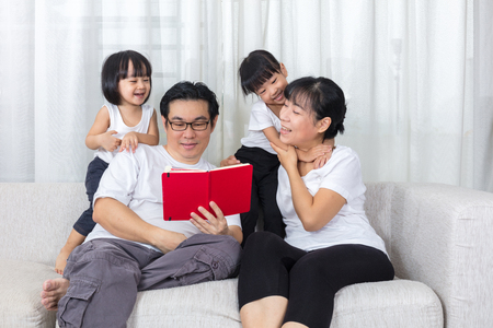Happy Asian Chinese family reading book on the couch in the living room at home.