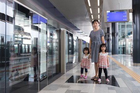 Asian Chinese mother and daughters waiting for transit at MRT station in Kuala Lumpur, Malaysia.