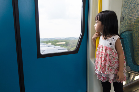 looking through window: Asian Chinese little girl inside a MRT transit looking far way beside the window.
