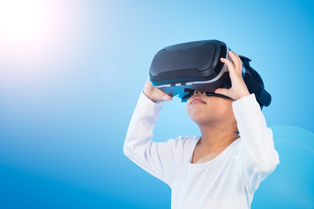 Asian Chinese little girl experiencing virtual reality eyeglassses in isolated background. Stock Photo