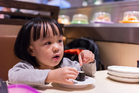 japanese people: Asian Chinese little girl eating sushi at a Japanese restaurant in the mall.