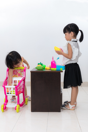 playing the market: Asian Chinese little sisters pretending as customer and cashier with trolley toys in isolated white background.