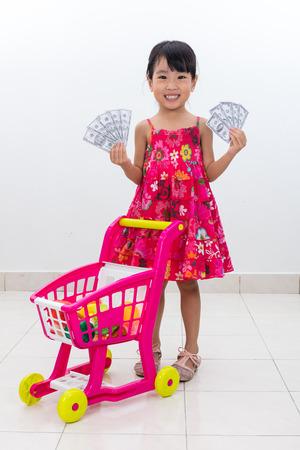 La niña china asiática feliz que empuja la carretilla del juguete que sostiene efectivo adentro aisló el fondo blanco. Foto de archivo