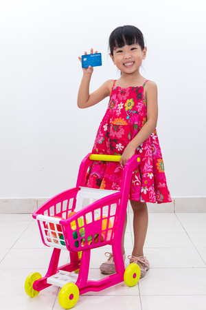 Happy Asian Chinese little girl pushing toy trolley holding credit card in isolated white background. Stock Photo