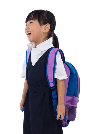 schoolbag: Happy Asian Chinese little girl wearing primary school uniform with school bag in isolated white background.
