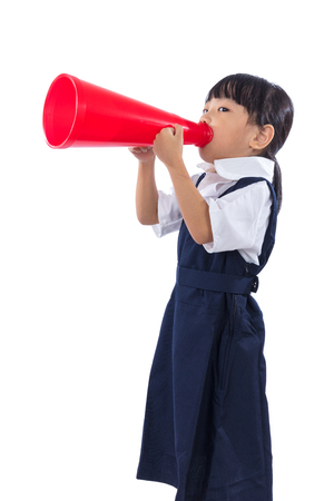 Asian Chinese little primary school girl holding retro megaphone in isolated white background.