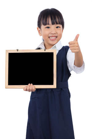 Asian Chinese little primary school girl holding chalkboard with thumbs up in isolated white background 스톡 콘텐츠