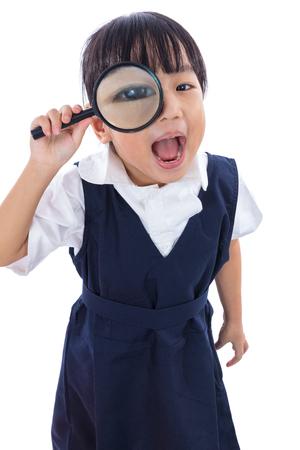 escuela primaria: Feliz asiática china niña de la escuela primaria con lupa en el fondo blanco aislado.