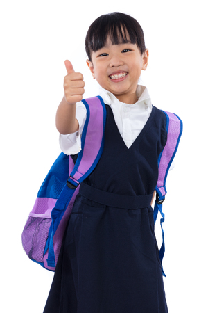 Asian Chinese little primary school girl with school uniform showing thumbs up in isolated white background. 版權商用圖片