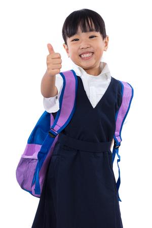 Asian cinese piccola scuola primaria scuola con uniforme scolastica mostrando i pollici in su sfondo bianco isolato. Archivio Fotografico - 68548578