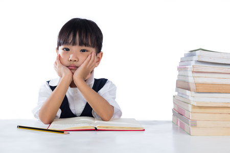 Boring Asian Chinese little girl wearing school uniform studying in isolated white background.