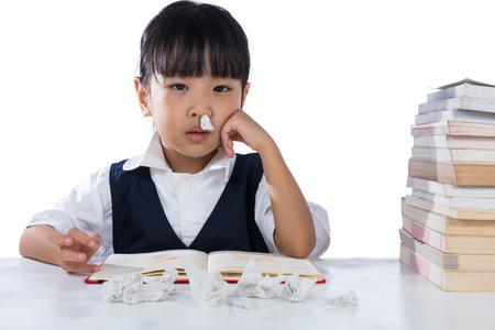 Enfermo de Asia chino niña que llevaba uniforme de estudiar en el fondo blanco aislado.
