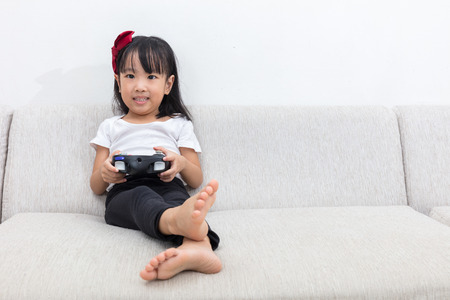 Asian Chinese little girl playing TV games on the sofa in the living room at home alone.