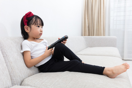 Asian Chinese little girl holding a TV remote control sitting on the sofa in the living room at home.
