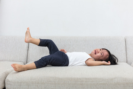 argue kid: Asian Chinese little girl crying on the sofa in the living room at home.
