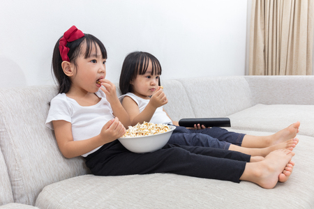 female child: Asian Chinese little sisters eating popcorn on the sofa in the living room at home.