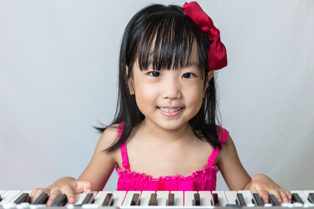 Asian Chinese little girl playing electric piano keyboard in isolated white background. Stock Photo