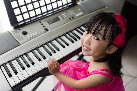 Niña asiática china feliz que juega el teclado de piano eléctrico en la sala de estar en casa.
